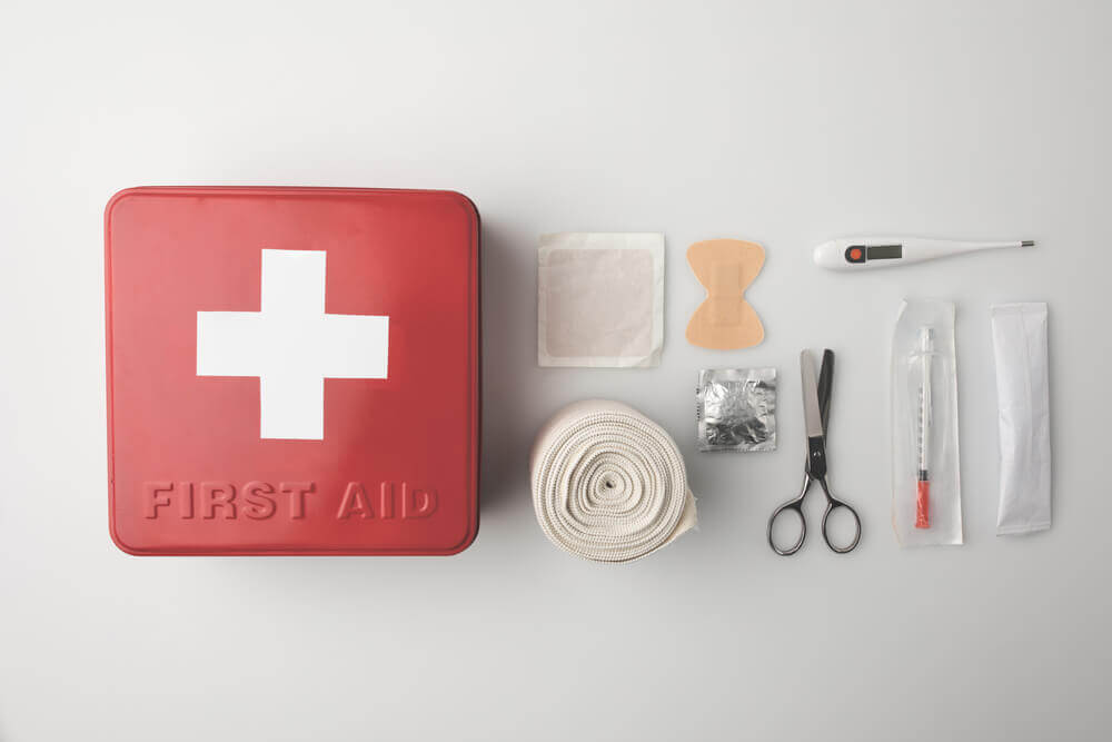 Find out how to make a first aid kit for travel by top family travel blog Marcie in Mommyland. Image of a red first aid kit plus supplies and tools.