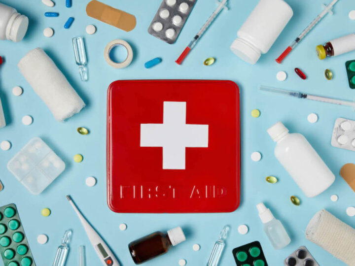 Find out what to pack in a family travel first aid kit for kids by top family travel blog Marcie in Mommyland. Image of a red first aid kit surrounded by medical supplies.