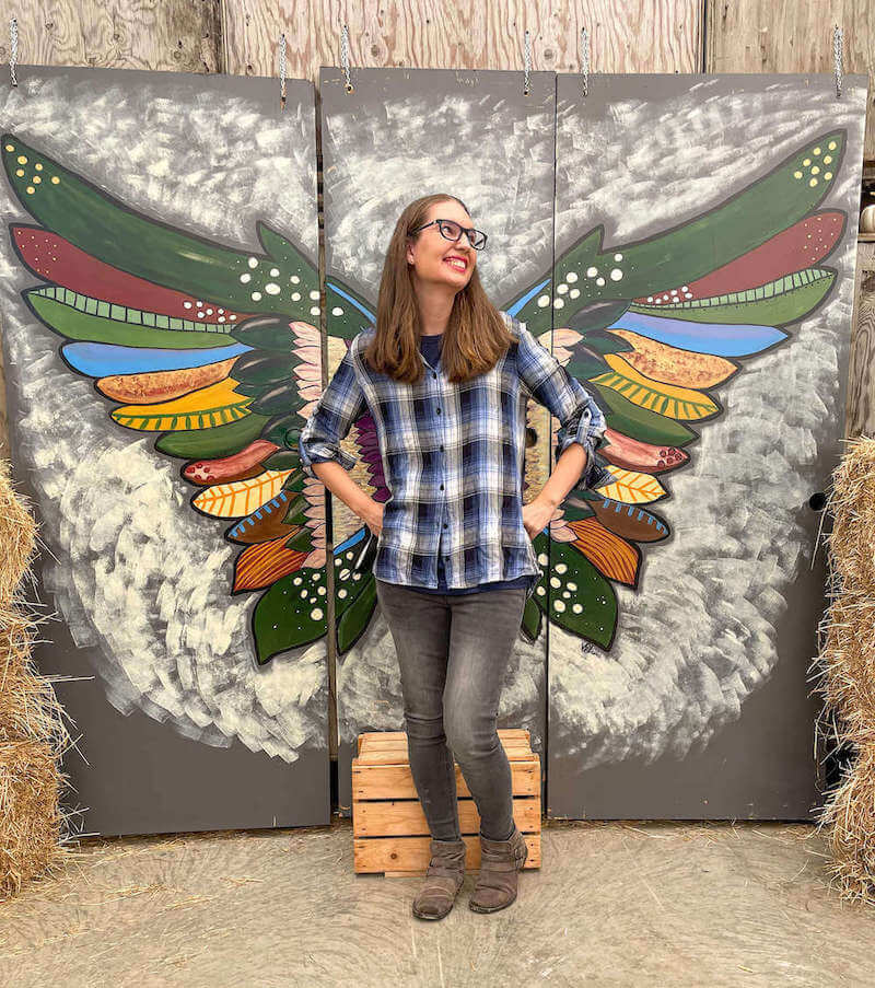 Image of a woman wearing a plaid shirt posing in front of an angel wings photo wall.