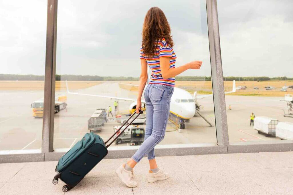 Many Hawaii travel insurance companies will cover airline changes. Image of a woman rolling a suitcase at a gate with an airplane in the background.