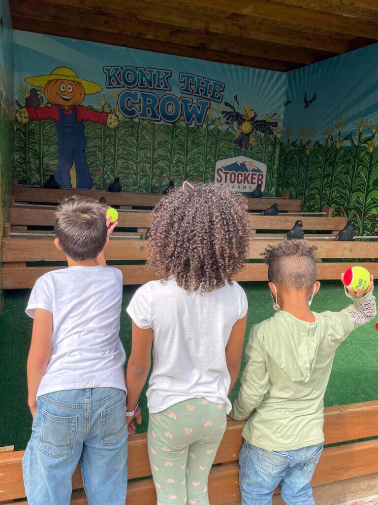 Image of three kids throwing balls at fake crows at a carnival game at Stocker Farms in Washington State.