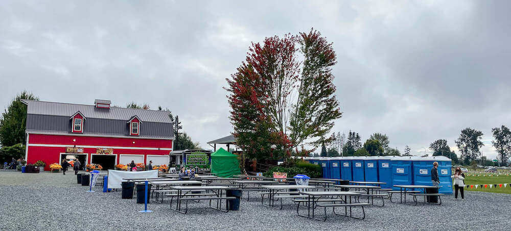 Image of picnic tables outside with port-a-potties in the background.