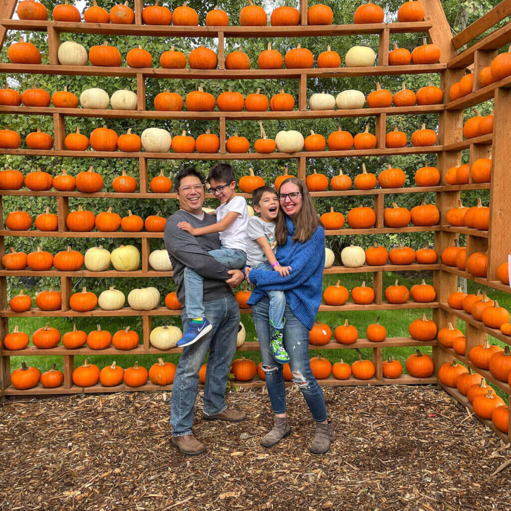 Image of a family smiling inside a pumpkin barn.