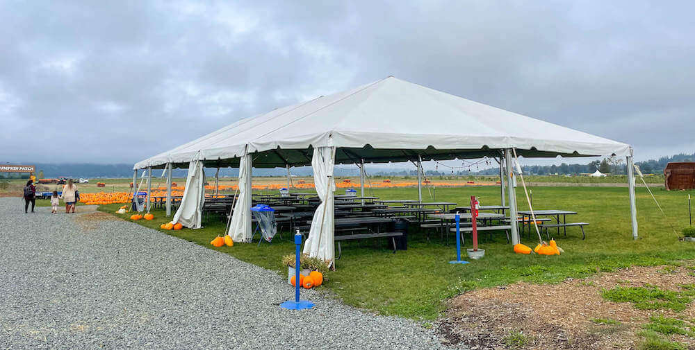 Large tent with picnic tables underneath.